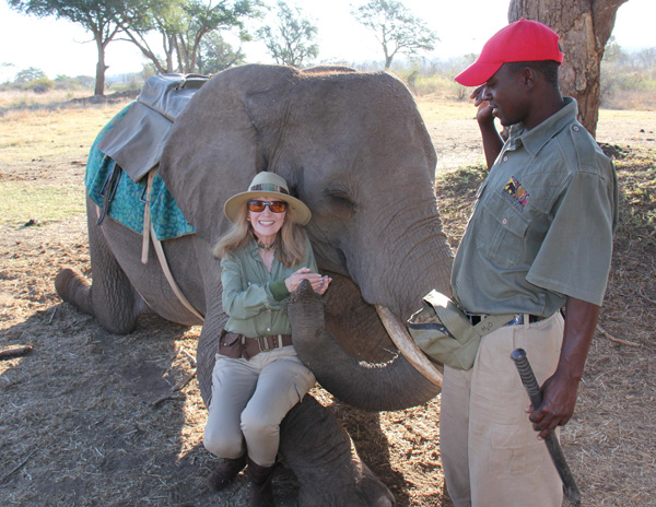 Joany sitting on Elephant's leg after an Elephant Safari, in Victoria Falls, Zimababwe, Africa